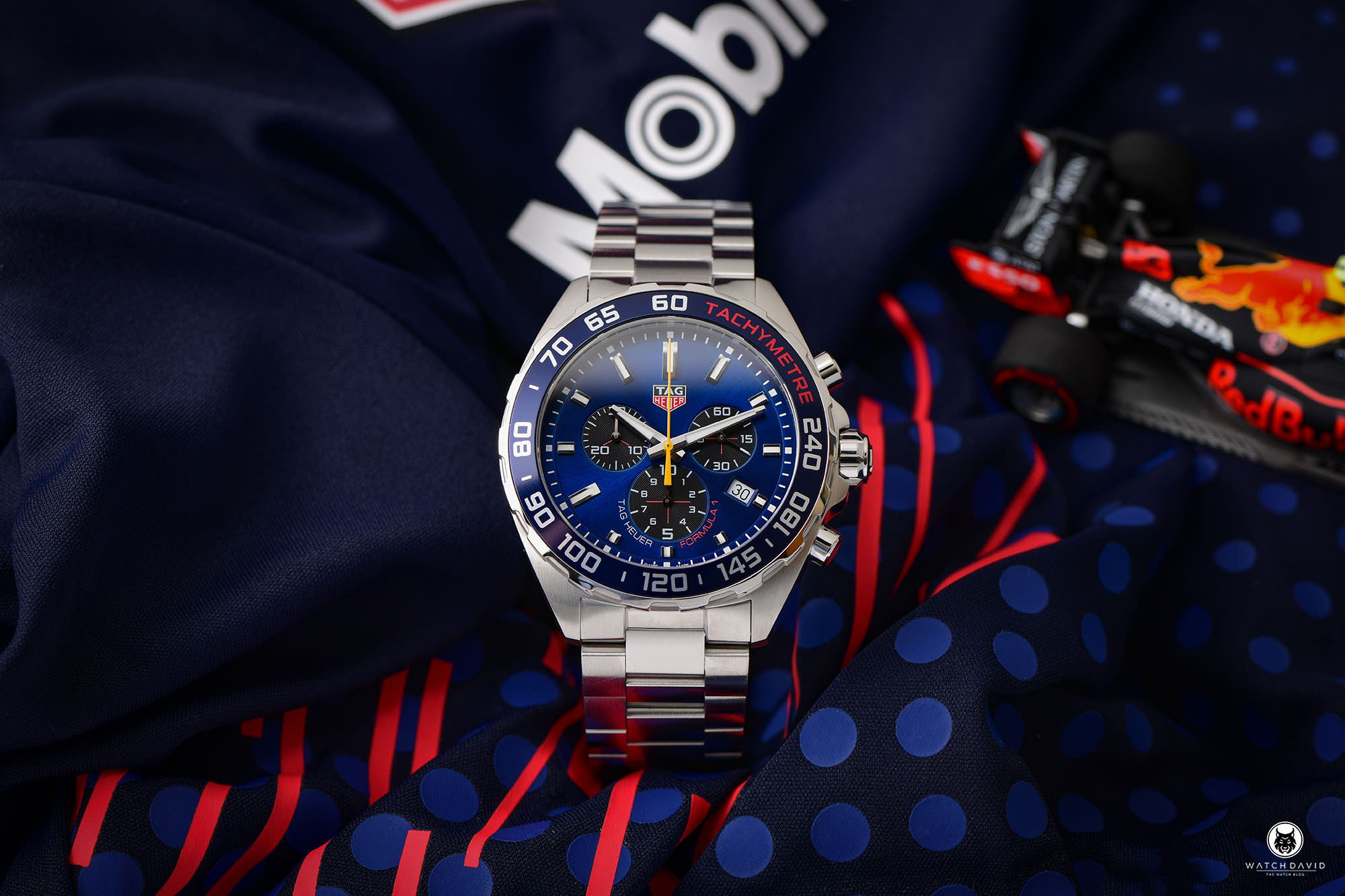 The TAG Heuer Aston Martin Red Bull is part of the Formula 1 collection that the Swiss watchmaker released together with Red Bull Racing. An exciting daily rocker with racer genes or rather something for die-hard Formula 1 fans? I took a closer look at the quartz chronograph for you. Your online store for luxury watches: the Uhrenlounge Nowadays, luxury watches from well-known manufacturers are usually bought on the Internet. Especially here it is important to find a suitable and reputable provider. This is where the Uhrenlounge comes into play. For this review, I once again collaborated with the online portal of Aika Juweliere Dresden, who kindly provided me with the TAG Heuer Aston Martin Red Bull. It's worth a look at the homepage! The Uhrenlounge carries more than twenty selected brands on their site, so everyone should find what they are looking for. You can also order TAG Heuer's Aston Martin Red Bull there. As always, you'll find all the important links at the end of this review! Why you should watch Formula 1 again! At the moment it is worth to watch Formula 1. This is not only due to the world championship battle, which has gained in excitement again in the 2021 season, but also due to the advertising - right, the watch advertising. You can find them on boards, as sponsor stickers on the cars, and last but not least on the wrists of the drivers, pretty much every one of them is equipped with a luxury watch. Watch brands and Formula 1 – that fits!. No wonder, precision, perfection and performance are probably characteristics that are highly appreciated on both sides. In recent years, this has led to more and more manufacturers finding their way into Formula 1. While Rolex, for example, is the main sponsor of the series, most racing teams also have a designated watch partner. Mercedes IWC, Ferrari and McLaren Richard Mille and four-time world champion Red Bull TAG Heuer. The traditional Swiss company and the Austrian racing team have been cooperating for seve